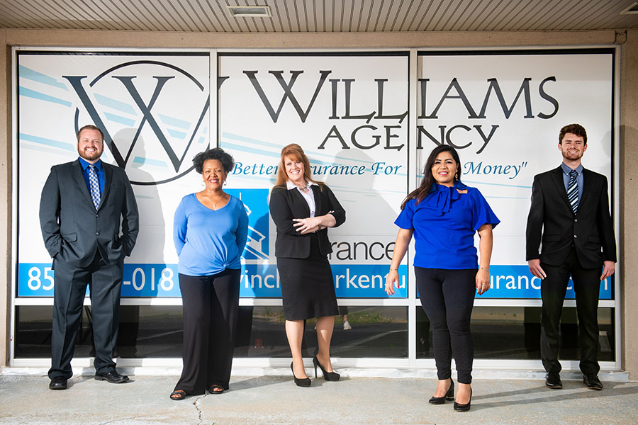 Meet Our Team - Portrait of Williams Agency Team Standing in Front of Agency Sign