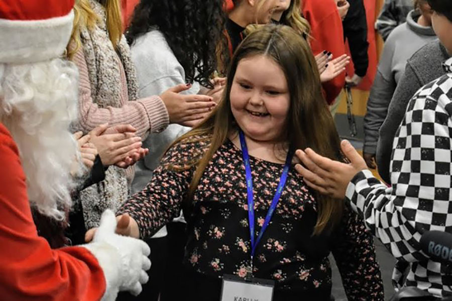 Community Involvement - Excited Girl Shaking Hands with Santa Claus During Sleep Dreams Event